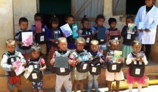 Chères Marraines, Chers Parrains, La période que nous venons de traverser a bouleversé nos vies et celles de millions de personnes à travers le monde, renforçant cette conviction que nous avons également toutes et tous un rôle important à jouer pour aider les enfants à sortir de la précarité. Et lorsque le contexte sanitaire accentue encore plus les disparités, le parrainage permet de mieux les protéger et les accompagner. Merci à vous d'être à nos côtés. A Madagascar, les écoles que nous soutenons ont commencé à rouvrir dès mai, et les activités de nos programmes ont pu progressivement se remettre en route, avec une mobilisation toute particulière des équipes terrain pour répondre à la situation d'urgence sanitaire mondiale. Aujourd'hui, nous sommes heureux de pouvoir vous envoyer des nouvelles de vos filleuls que nous n'avions pu vous transmettre en raison du confinement. Et c'est également l'occasion de vous confirmer la reprise des correspondances avec les enfants par courrier. Merci beaucoup pour votre patience, nous savons à quel point il est important pour vous, comme pour les enfants, de garder le lien, particulièrement depuis ces derniers mois. Grande nouveauté, désormais, les courriers pour votre filleul.e sont à envoyer directement à Madagascar ! Nous vous donnons toutes les indications [au verso de ce courrier]. N'hésitez pas à leur écrire, ils sont tout aussi impatients que vous d'avoir de vos nouvelles ! Il était également important de vous transmettre le bilan des actions 2019 qui ont pu être mises en place, grâce à vous, marraines et parrains, et avec le soutien de nombreux donateurs et entreprises solidaires. Un grand merci pour votre mobilisation et votre engagement qui nous ont permis de répondre aux besoins des enfants et de leur famille en termes d'éducation, de nutrition et de développement agricole, mais aussi de répondre présent et efficacement auprès d'eux depuis la période de crise sanitaire liée à la covid-19. Enfin, nous voulions très sin